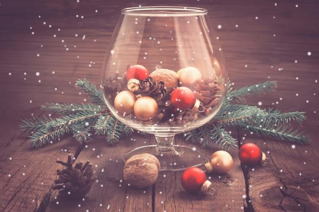 Carte de noël vintage. pommes de pin, noix et jouets de noël dans le verre