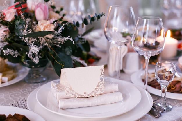 Carte avec le nom de l'invité se trouve sur une assiette