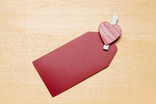 Carte de nom de la saint-valentin simple minimaliste avec petite épingle de coeur rouge sur une surface en bois beige