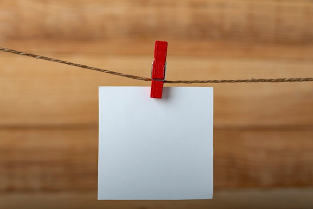 Une carte de note blanche vide suspendue avec une pince à linge sur une cheville de corde. cadre vertical. fond en bois.