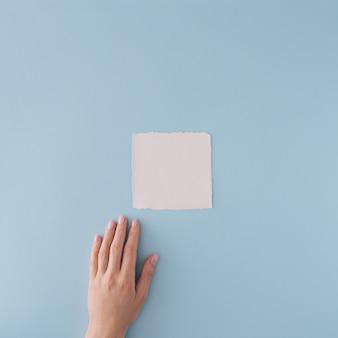 Carte en papier blanc et la main sur fond bleu pastel. mise à plat minimale.