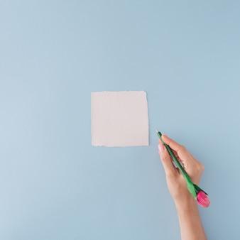 Carte en papier blanc et la main tenant le stylo sur fond bleu pastel. mise à plat minimale.
