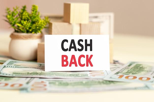 La carte en papier blanc avec le texte cash back est sur la surface du papier-monnaie, des cubes en bois et des fleurs