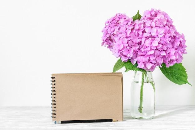 Carte de papier de mariage avec bouquet de fleurs d'hortensia rose dans un vase.