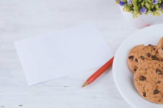 Carte de papier vide avec stylo rouge et biscuits