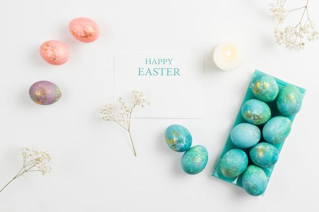 Carte de pâques joyeux. composition minimaliste élégante de turquoise avec des oeufs de pâques en or sur fond blanc. bougies et délicates fleurs de printemps. mise à plat, vue de dessus, espace copie.