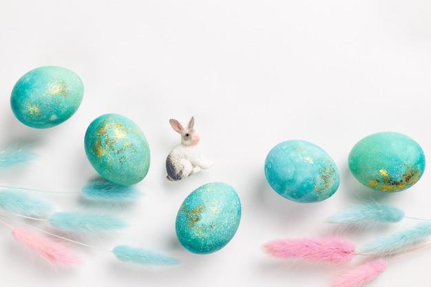 Carte de pâques joyeux. composition minimaliste élégante de turquoise avec des oeufs de pâques en or sur fond blanc. figurine de lapin et délicates fleurs printanières. mise à plat, vue de dessus, espace copie