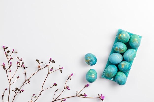 Carte de pâques joyeux. composition minimaliste élégante de turquoise avec des oeufs de pâques en or sur fond blanc. fleurs de printemps délicates. mise à plat, vue de dessus, espace copie.