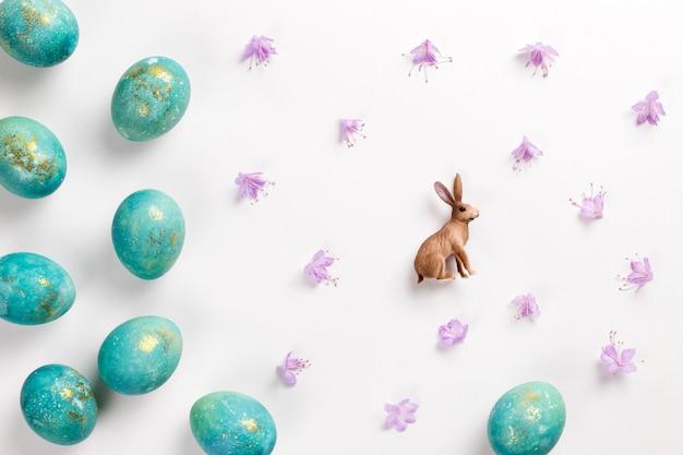 Carte de pâques joyeux. composition minimaliste élégante de turquoise avec des oeufs de pâques en or sur une surface blanche. figurine de lapin et délicates fleurs printanières. mise à plat, vue de dessus, espace copie