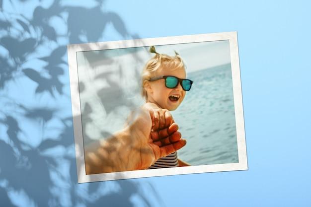 Une carte photo blanche avec un enfant sur un mur de couleur bleu safran avec une ombre d'un arbre