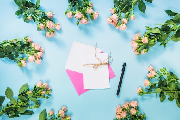 Carte; plume et enveloppe rose entourée de bouquet de roses roses sur fond bleu
