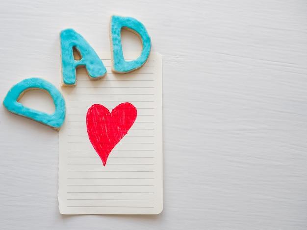 Carte postale avec un coeur peint en rouge et un mot papa