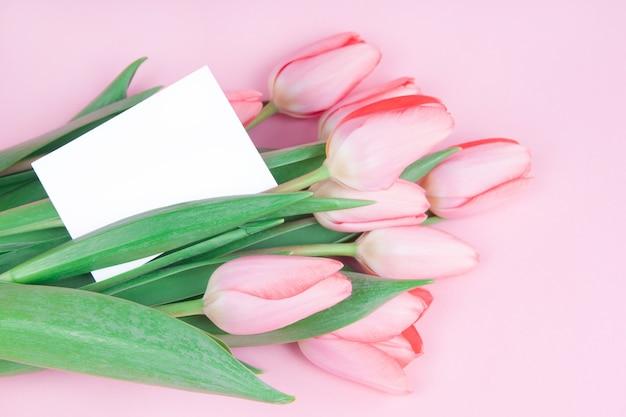 Carte postale délicate fleurs tulipes avec une note sur un fond rose maquette