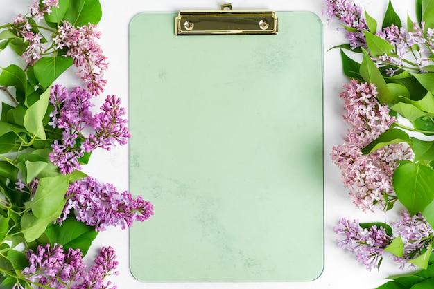 Carte postale du cadre de fleurs lilas fraîches et presse-papiers pour papier sur un fond de marbre gris clair. vue de dessus.