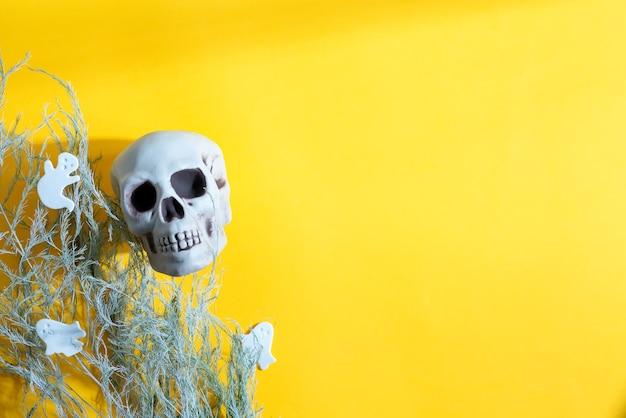 Carte postale de fête d'halloween décorative avec crâne humain, plantes sèches et fantômes coupés en papier sur fond jaune, espace de copie. vue de dessus.