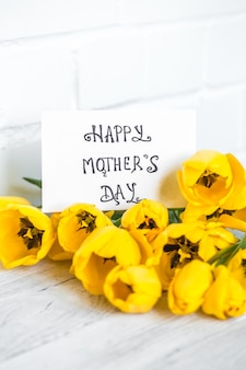 Carte postale fête des mères et tulipes jaunes sur fond de bois clair, concept de vacances