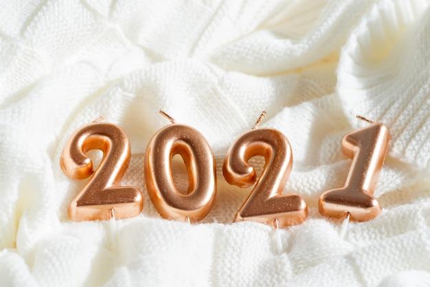 Carte postale de noël festive créative avec des bougies de décoration chiffres 2021 sur un tissu à tricoter blanc
