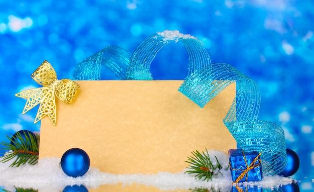Carte postale vierge, boules de noël et sapin sur fond bleu