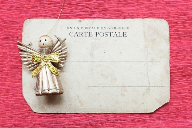 Carte postale vintage avec figure d'ange jouet sur fond de papier rouge
