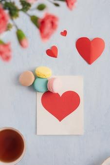 Carte postale de voeux coeur rouge avec des fleurs. vue de dessus. mise à plat.