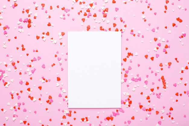 Carte présente avec des coeurs roses et rouges sur rose