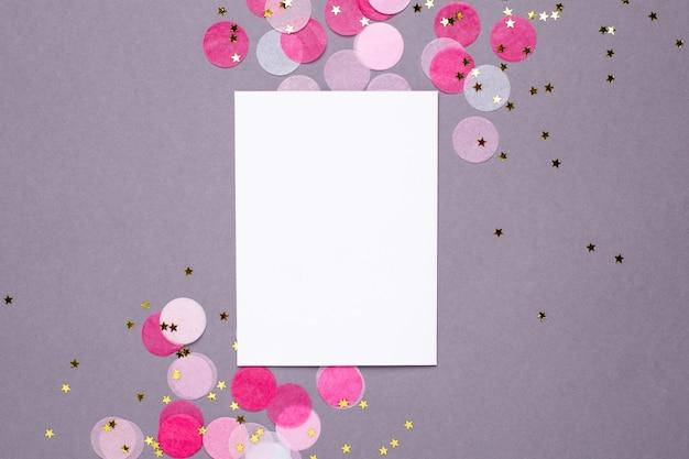Carte présente et confettis roses avec des étoiles dorées sur fond gris