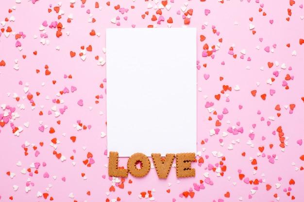 Carte présente avec des lettres de biscuits amour et rose, coeurs rouges sur rose