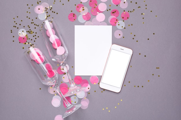 Carte présente, maquette de téléphone portable et confettis roses avec des étoiles dorées sur fond gris