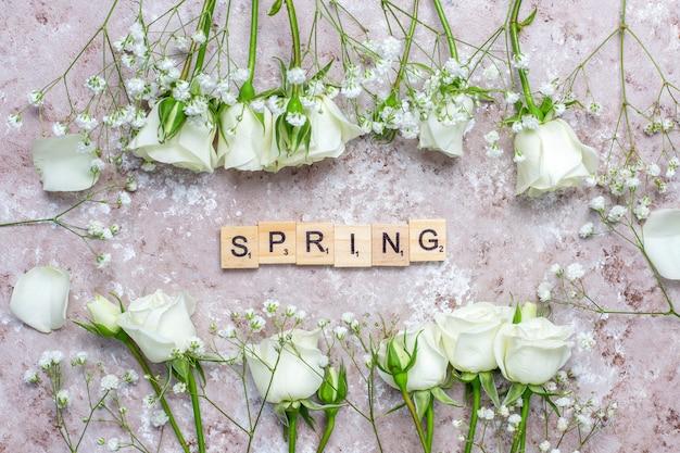 Carte de printemps avec des roses blanches et des fleurs, vue de dessus