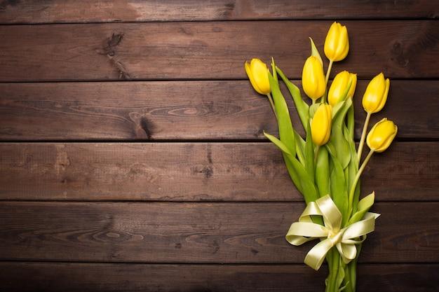 Carte de printemps: tulipes jaunes sur fond de bois foncé. vue de dessus, poser à plat.