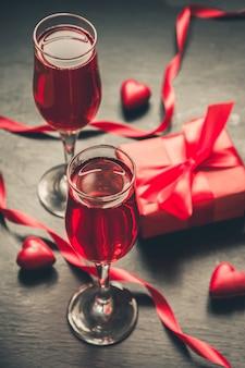 Carte de saint valentin avec champagne et bonbons coeur sur fond noir.