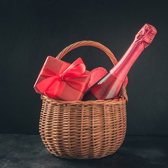 Carte de saint valentin avec champagne et cadeau rouge sur fond noir. espace pour vos salutations.