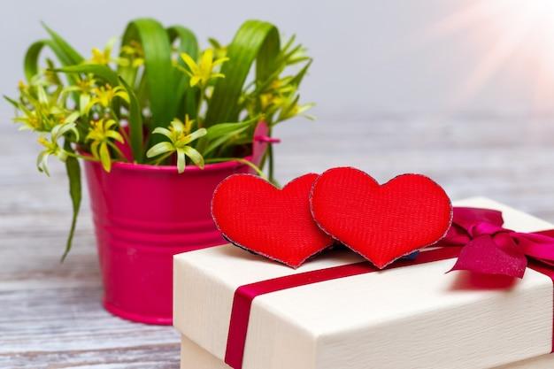 Carte de saint-valentin avec un coeur sur une boîte-cadeau près des fleurs dans un seau décoratif