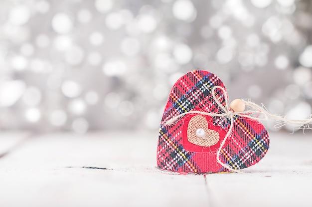 Carte de saint valentin avec coeur rouge sur bokeh argent abstrait
