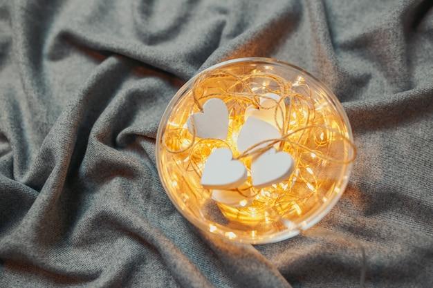 Carte de saint valentin. coeurs en bois blanc avec guirlandes lumineuses dans le bol sur le fond gris. assiette avec coeurs et lumières.