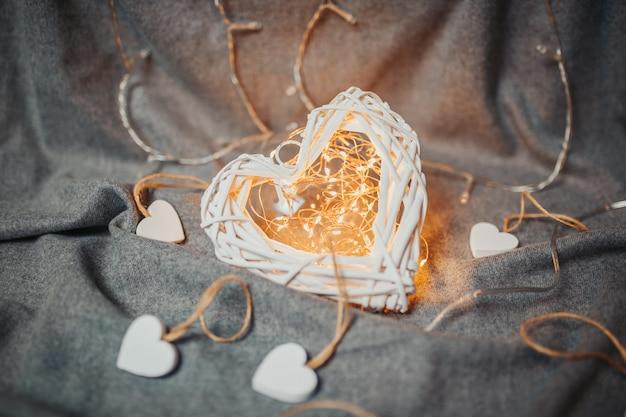 Carte de saint valentin. coeurs en bois blancs sur fond gris. coeurs avec guirlande lumineuse. grand coeur lumineux avec de petits coeurs autour.