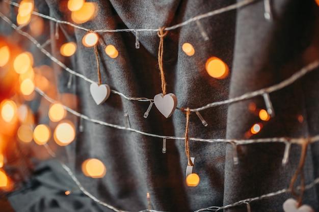Carte de saint valentin. coeurs en bois blancs sur fond gris. coeurs avec guirlandes lumineuses et matière grise en arrière-plan.