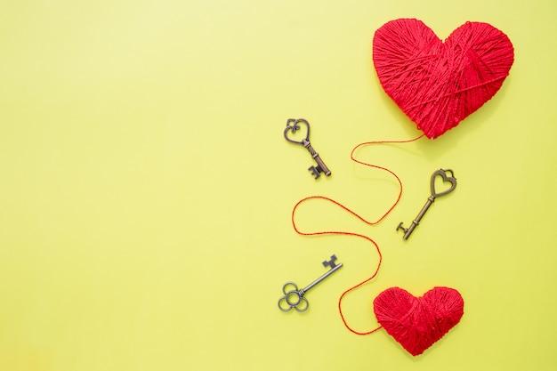 Carte de saint valentin avec coeurs rouges et clé sur fond jaune