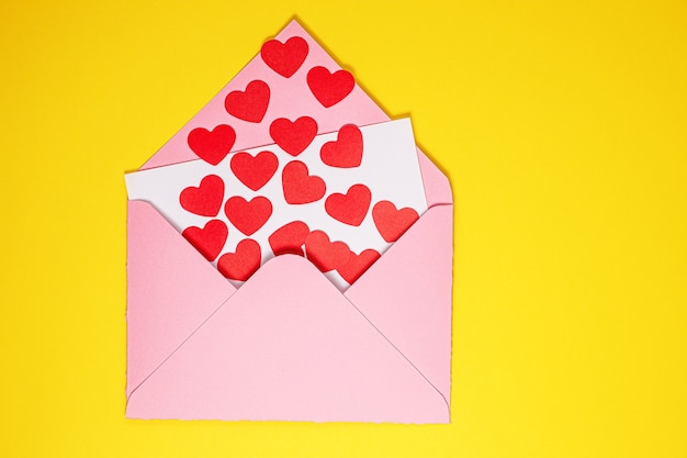 Carte de saint valentin. des coeurs rouges en papier s'envolent d'une enveloppe en papier rose sur fond jaune. art du papier le jour de la saint-valentin. papier découpé et style artisanal. espace pour le texte. concept de la saint-valentin