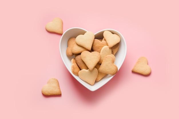 Carte de saint valentin avec des cookies en forme de coeur fait maison sur la vue de dessus rose