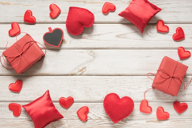 Carte de saint valentin. décor rouge, coeurs, cadeaux sur planche de bois blanc et fond. vue de dessus.