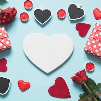 Carte de saint valentin avec un espace pour le texte et un ensemble de boîte-cadeau, roses rouges sur fond bleu pastel.