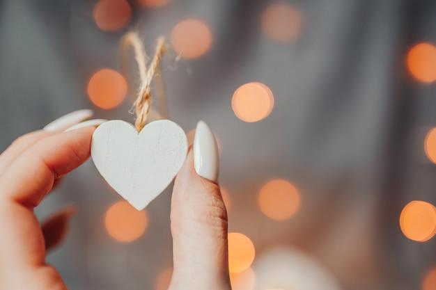Carte de saint valentin. la femme détient de nombreux coeurs en bois blancs sur le fond clair. coeurs avec guirlande lumineuse bokeh.