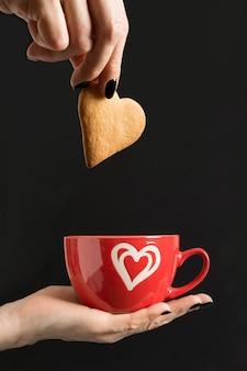 Carte de saint valentin. femme tenant une tasse de café rouge et mettre des cookies. isolé sur fond noir. concept.