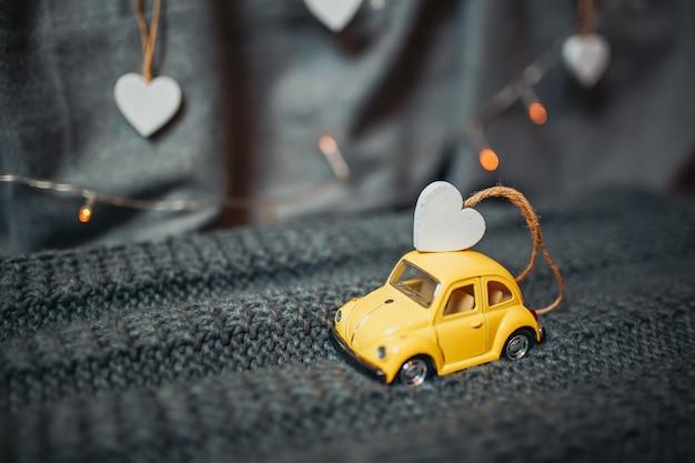Carte de saint valentin. petite voiture jaune avec un petit cœur en bois sur le toit. jouet volkswagen beetle jaune avec guirlandes lumineuses en arrière-plan.