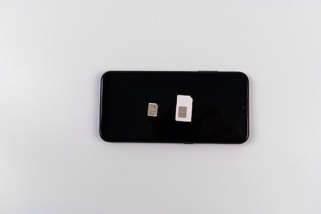 Carte sim, clip de clé sur smartphone noir sur fond blanc. communications mobiles. internet sans fil 3g, 4g.