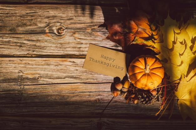 Carte de thanksgiving bouquet de feuilles d'érable rouge jaune vif et citrouille sur fond de bois
