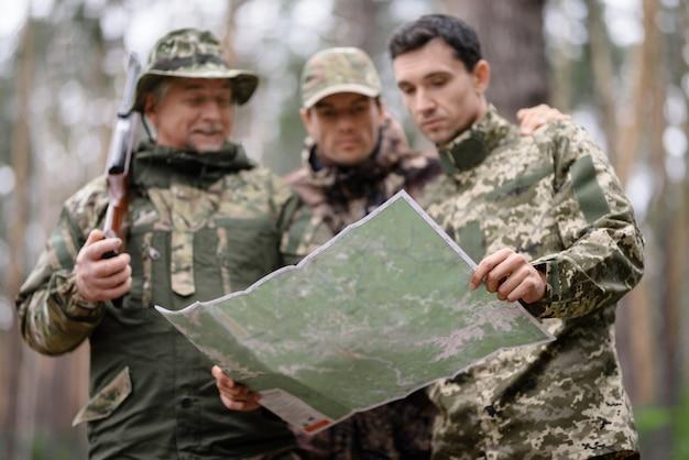 Carte topographique en mains de chasseurs en forêt.