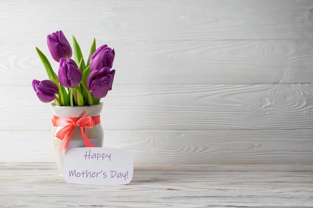 Carte de vacances de la fête des mères avec un bouquet de tulipes violettes fraîches dans un vase avec un arc rose