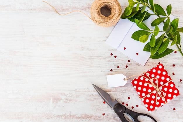Carte vide attachée sur une boîte cadeau en pointillé rouge sur bois blanc, fond.
